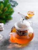 Exponeringsglastekanna med blommor bundet te, varmt te i exponeringsglastekanna och honung med metallhonungpinnen på stenbakgrund royaltyfri fotografi