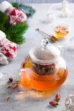 Exponeringsglastekanna med blommor bundet te, varmt te i exponeringsglastekanna och honung med metallhonungpinnen på stenbakgrund arkivbild