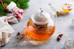 Exponeringsglastekanna med blommor bundet te, varmt te i exponeringsglastekanna och honung med metallhonungpinnen på stenbakgrund arkivbilder