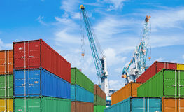 Export or import shipping cargo container stacks. And port cranes Royalty Free Stock Photo