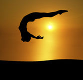 Exposed. Silhouette of woman back diving on brilliant sunset background Stock Photography