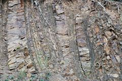 Exposed Sedimentary Rock layers on Greek Mountain Slope. Shattered exposed sedimentary rock layers on Greek mountain slope, almost vertical and distorted by royalty free stock image