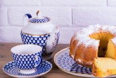 Exposição do copo da torta de maçã do chá e chaleira na tabela de madeira e fundo branco do tijolo, xícara de chá da porcelana do Fotos de Stock Royalty Free