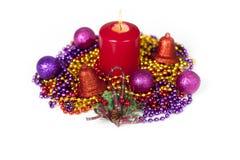 Exposição do Natal com uma vela vermelha que queima-se no meio das correntes do grânulo Foto de Stock Royalty Free