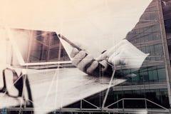 exposição dobro da mão do homem usando auriculares de VOIP com tabl digital Foto de Stock
