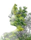 Exposição dobro da menina bonita nova entre as folhas e as árvores silhueta isolada no branco Fotos de Stock