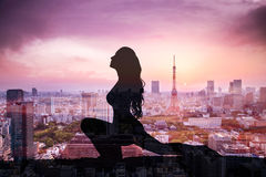 Exposição dobro da mulher da ioga da silhueta contra a cidade do Tóquio imagem de stock royalty free