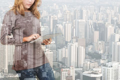 Exposição dobro da mulher que usa a tecnologia da tabuleta e a construção urbana foto de stock