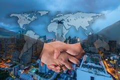 Exposição dobro de um aperto de mão do homem de negócios no mundo Carto global Imagem de Stock Royalty Free