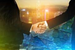 Exposição dobro do aperto de mão entre o homem de negócios e a mulher de negócios com arquitetura da cidade e dinheiro do EURO imagem de stock