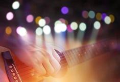 Exposição dobro do bokeh colorido com a imagem da luz do concerto e a mão masculina que jogam na guitarra acústica foto de stock