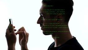 Exposi??o dobro do hacker que usa o smartphone com c?digo verde nele Exposi??o dobro do programador do homem que usa o telefone e vídeos de arquivo