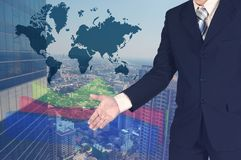 Exposição dobro do homem de negócios que agita a mão com carta do gráfico do crescimento e fundo borrado da construção e do mundo imagem de stock royalty free
