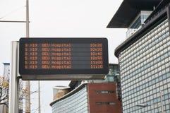 Exposição eletrônica do horário em uma parada do ônibus típica imagens de stock