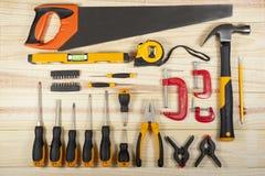 Exposição lisa da configuração do conjunto de ferramentas de um trabalhador em um fundo do wodden Fotos de Stock Royalty Free