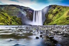 Exposição longa da cachoeira famosa de Skogafoss em Islândia no crepúsculo