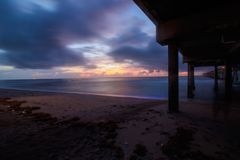 Exposição longa da tempestade do nascer do sol de Dania Beach sob Dania Pier Imagem de Stock