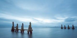 Exposição longa do rio com postes de amarração Foto de Stock Royalty Free