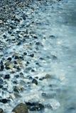 Exposição longa Mar que dobra acima sobre rochas cintilando imagens de stock