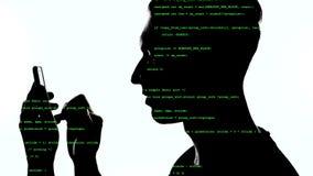 Exposi??o dobro do hacker que usa o smartphone com c?digo verde nele Exposi??o dobro do programador do homem que usa o telefone e video estoque