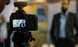 Exposi??o ou monitor da entrevista video do tiro da c?mera de DSLR em uma feira profissional fotos de stock royalty free
