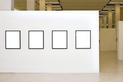 Exposición con cuatro marcos vacíos en las paredes blancas Imagenes de archivo