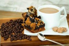 Exposición de la empanada del caramelo cerca de la taza de café blanca con los granos del azúcar y de café en la tabla de madera  Imagenes de archivo