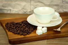 Exposición de la taza de café blanca con los granos del azúcar y de café en la tabla de madera y el fondo blanco de la pared de l Imágenes de archivo libres de regalías