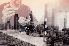 exposición doble de la mano del hombre usando las auriculares de VOIP con el tabl digital Fotografía de archivo