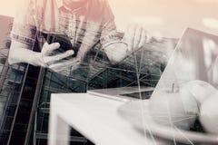 exposición doble de la mano del inconformista usando compter y móvil del ordenador portátil Fotos de archivo libres de regalías