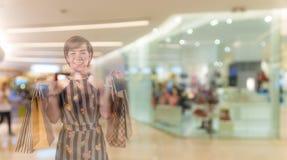 Exposición doble de la mujer feliz que hace compras en los grandes almacenes fotos de archivo