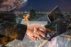 Exposición doble de un apretón de manos del hombre de negocios en la vista aérea del hig Foto de archivo