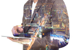Exposición doble de un hombre de negocios y de una ciudad usando una tableta encima foto de archivo libre de regalías