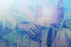 Exposición doble del hombre de negocios que usa las manos que mecanografían en un ordenador portátil en una cafetería Imagenes de archivo