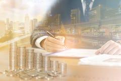 Exposición doble del hombre de negocios y paisaje urbano y monedas Foto de archivo