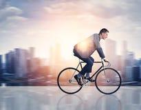 Exposición doble del hombre en una bicicleta y una ciudad fotografía de archivo libre de regalías
