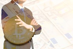 Exposición doble hombre de negocios con el bitcoin de oro en fondo euro de los billetes de banco foto de archivo