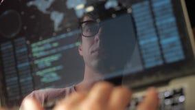 Exposición doble: programador del hombre en el funcionamiento de vidrios en un ordenador portátil El programador escribe el códig almacen de video