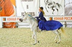 Exposición ecuestre internacional durante la demostración Jinete de la mujer en un vestido azul marino en un caballo blanco Fotografía de archivo