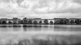 Exposición larga con las casas de la orilla del lago en ciudad Foto de archivo libre de regalías