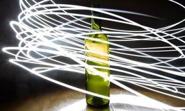 Exposición larga de la luz alrededor de una botella imagen de archivo