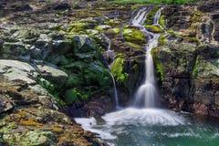 Exposición larga de una cascada rodeada por las algas y la alga marina coloridas fotos de archivo