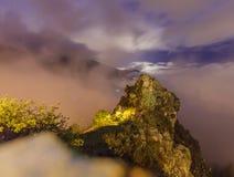 Exposición larga de una roca en las montañas francesas, encendida por la luna y una farola imágenes de archivo libres de regalías