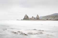 Exposición larga en la playa con las rocas Fotos de archivo libres de regalías