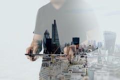 Exposición doble del hombre de negocios del éxito usando la tableta digital Imagen de archivo