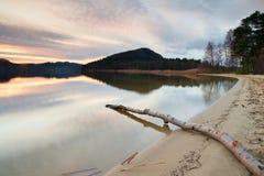 Exposición larga de la orilla del lago con el tronco de árbol muerto caido en la tarde del otoño del agua después de la puesta de Fotografía de archivo libre de regalías