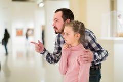 Exposiciones de exploración atentas del padre y de la hija en museo Imágenes de archivo libres de regalías