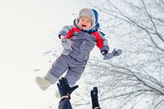 Exposing the child to air in winter, happy baby in winter clothes stock photo