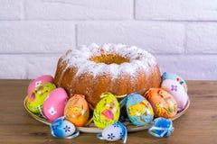 Expositie van Pasen-cake en kleurrijke eieren op houten lijst en de witte achtergrond van de brichmuur, beatuful Pasen-dag voor a Stock Afbeeldingen