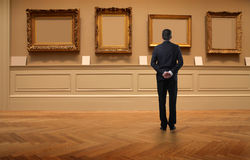 Exposition. Portrait of a man observing some empty frames at a picture exposition Royalty Free Stock Images